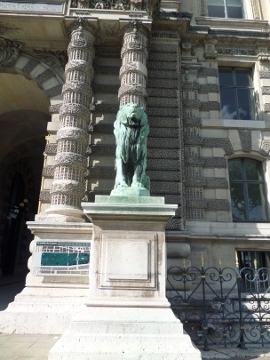 Lion stands guard outside Porte des Lions entrance along the Seine side.